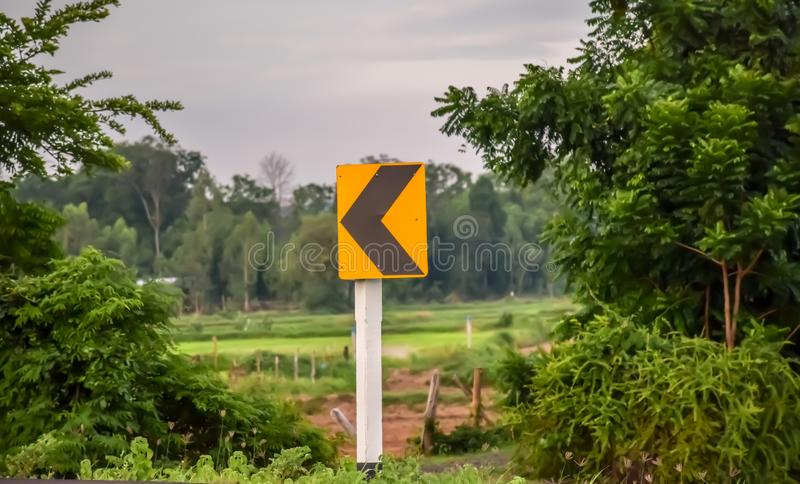 Traffic signs tell the curve on the side of the rural road. Nature stock photo