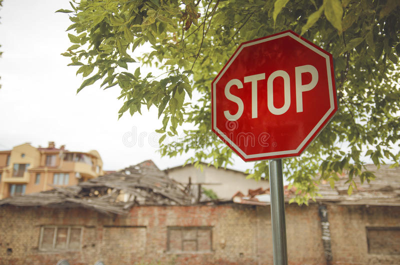 Traffic Stop Sign. Under Tree In Front Of Old Abandon Building royalty free stock image