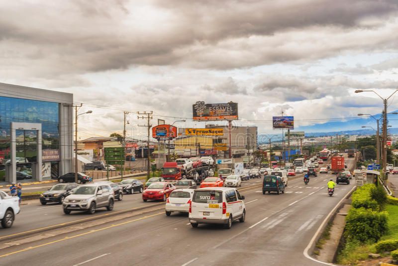 Traffic on the street in San Jose, Costa Rica. San Jose, Costa Rica - November 10, 2016: Cloudy sky above San Jose. Landscape view on the street and the stock photography