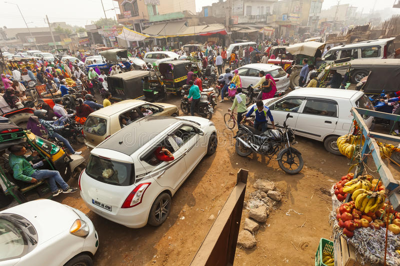 Traffic on the streets of a big mess. Taxis, mopeds and pedestrians cross without any order. Fruit sellers on the trading place. Gurgaon, India, November 1 stock photos