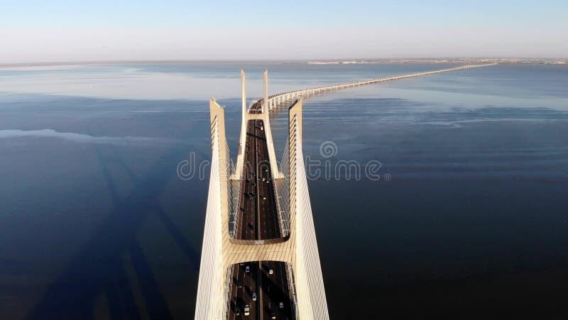 Traffic on Vasco da Gama bridge over the Tagus at sunset in Lisbon, Portugal, aerial view. stock image