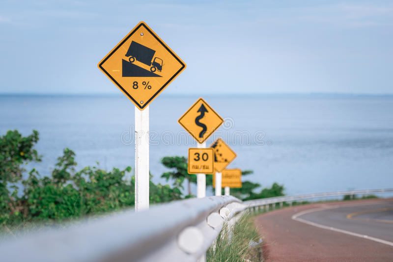 Traffic warning signs at the seaside road. Yellow warning signs placed at the hill of seaside road in Chantaburi, Thailand royalty free stock image