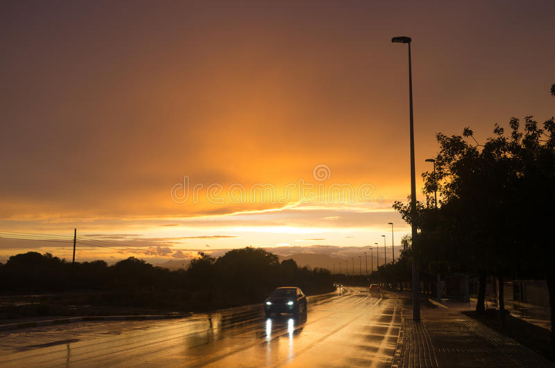 Wet road. Traffic on a wet road at sunset royalty free stock photography