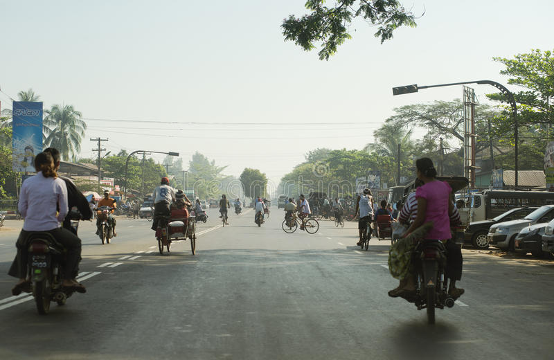 Traffic in Yangon - people riding scooters and bikes on a busy road stock photography