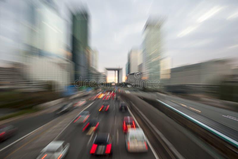 Traffichi con la luce della sfuocatura attraverso la città sulla strada principale urbana al crepuscolo B fotografia stock libera da diritti