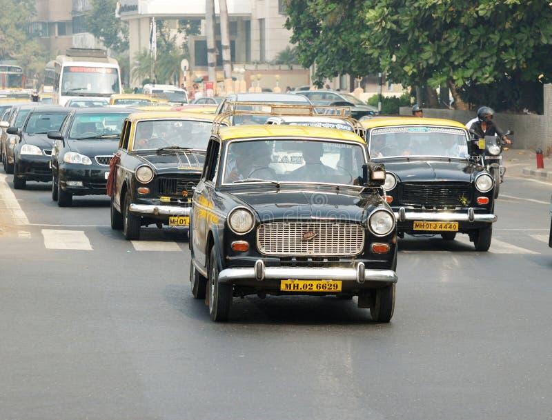 Traffico con parecchie carrozze classiche di ambasciatore, India di Mumbai fotografia stock libera da diritti