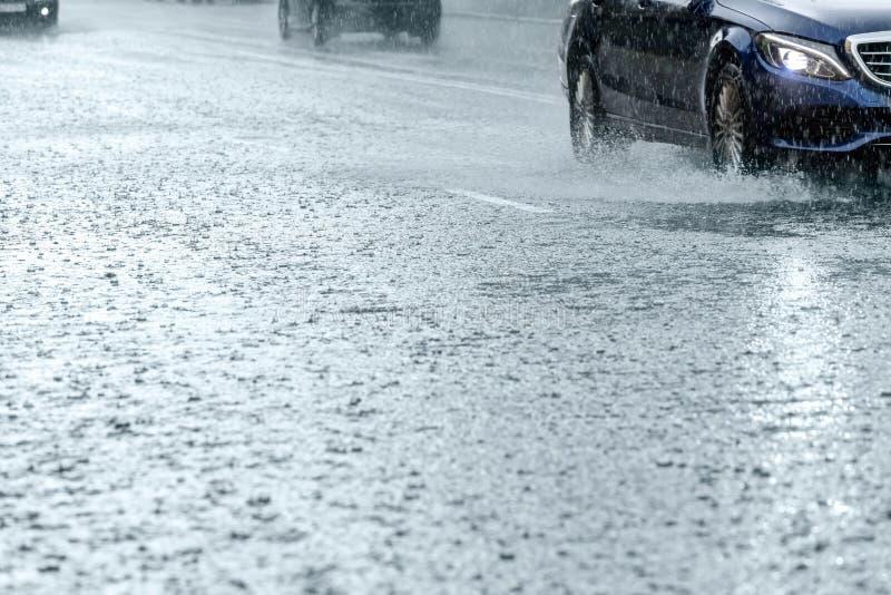 Traffico di automobile che guida sulla strada di città sommersa durante la pioggia fotografia stock libera da diritti