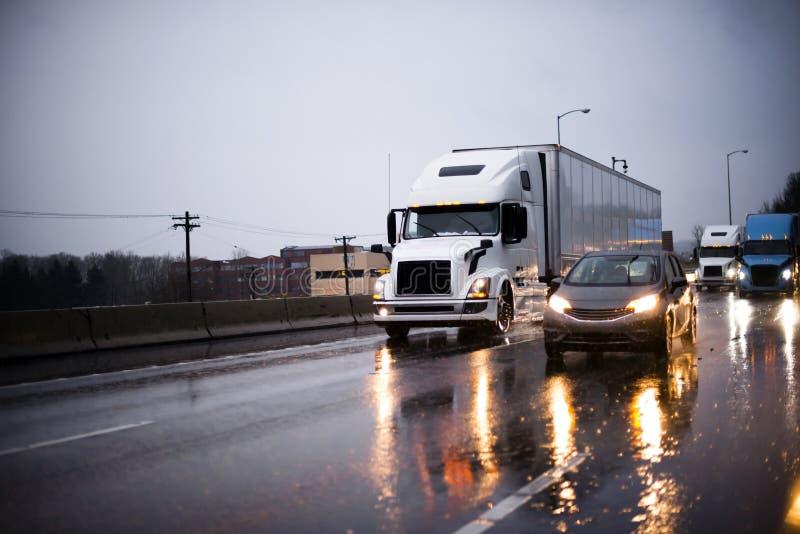 Traffico pesante con i grandi camion dei semi dell'impianto di perforazione e le altre automobili su highw fotografia stock libera da diritti