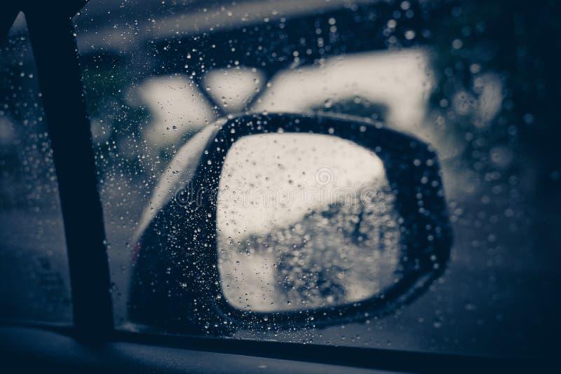 Traffico vago il giorno piovoso, finestra di automobile con le gocce di pioggia su vetro o il parabrezza fotografia stock
