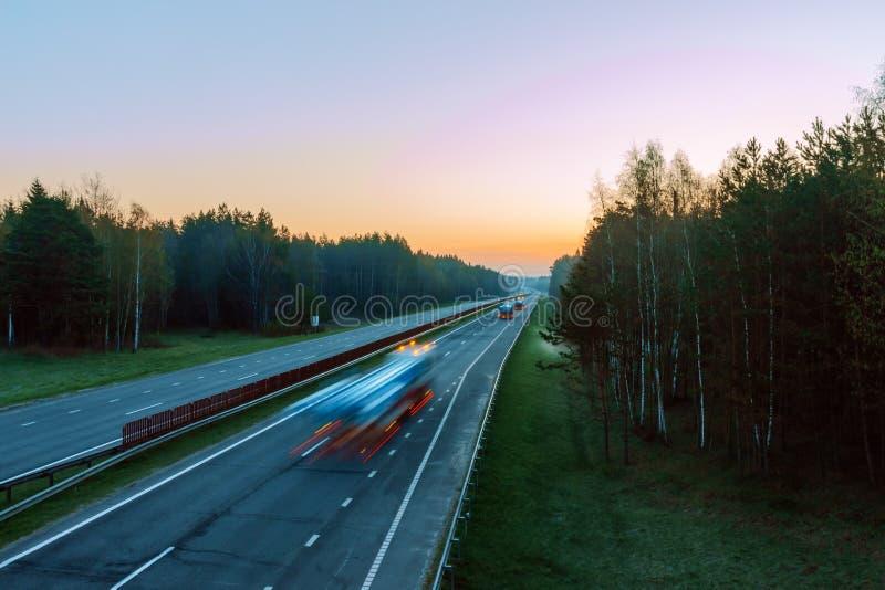 Traffico veloce sulla strada principale nel primo mattino immagini stock