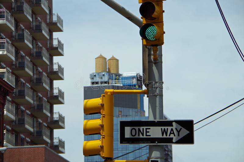 Trafic light and water towers. Traffic light and one way sign with water towers in nyc royalty free stock photo