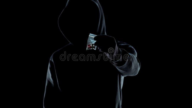 Traficante en la sudadera con capucha que muestra el paquete con las p?ldoras del lsd en la c?mara, problema del apego fotos de archivo