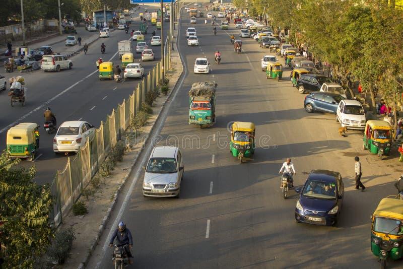 Trafik för indisk stad av den olika motoen och motorfordon mot bakgrunden av gröna träd, sikt från a royaltyfri bild