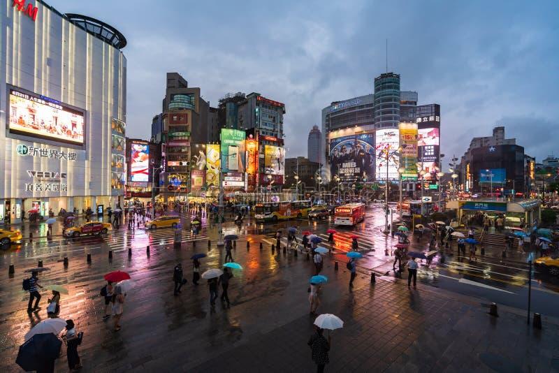 Trafik och folk som går på övergångsställe på Ximending med fallande regn i Taipei, Taiwan Ximending är det berömda modeet, natt fotografering för bildbyråer