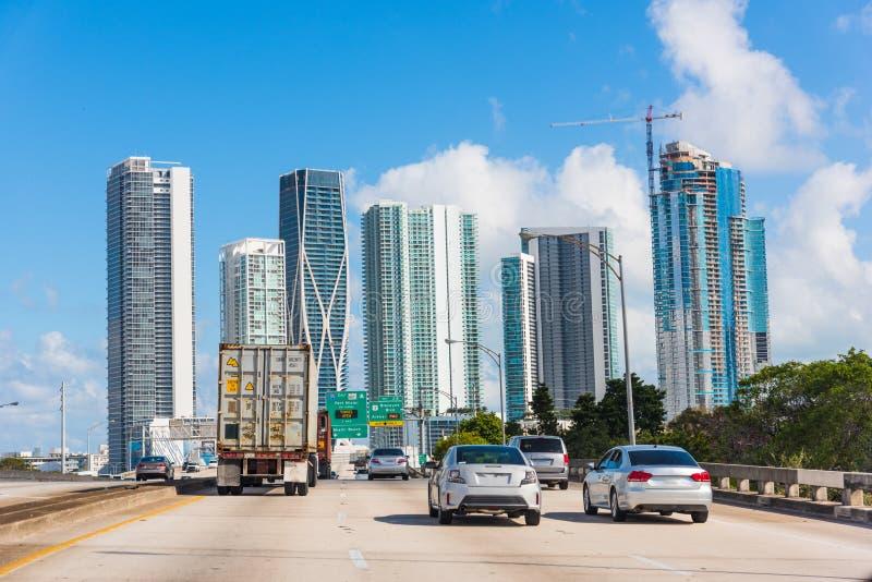 Trafik på huvudvägen med skyskrapor på bakgrunden royaltyfria bilder