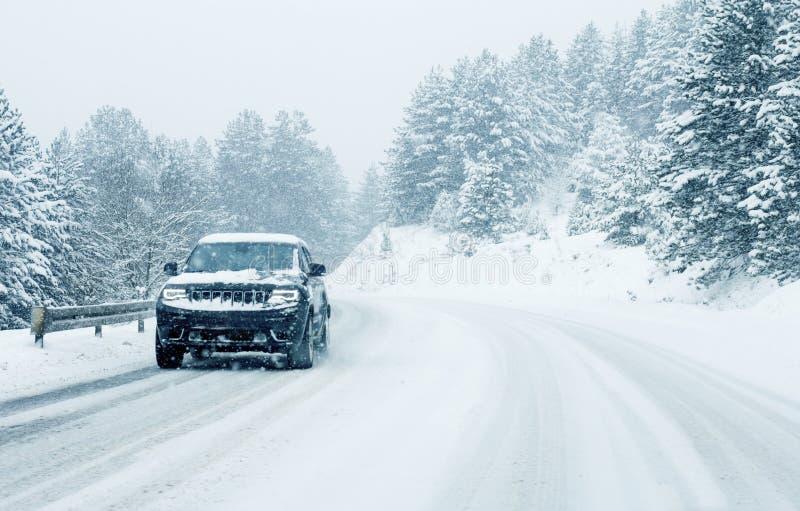 Trafikbil på vintervägen i snöhäftig snöstorm arkivbild