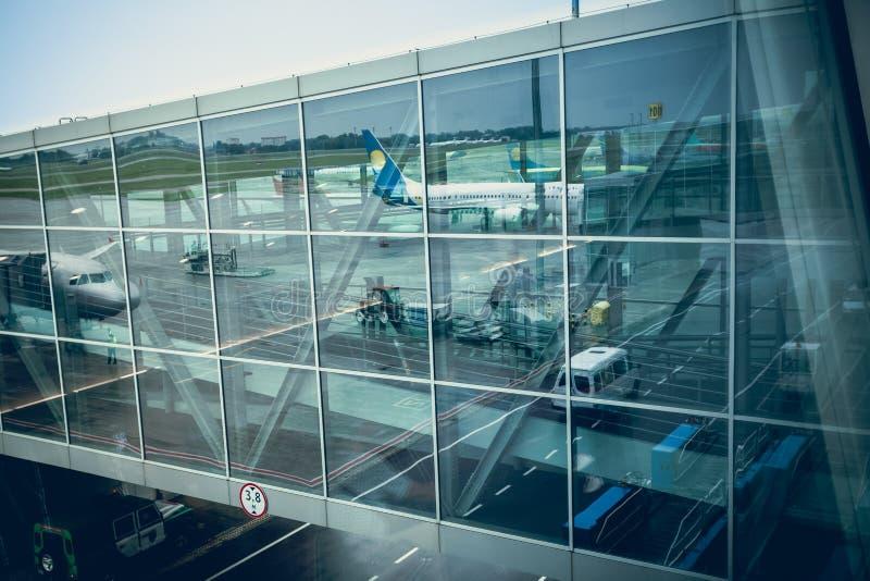 Trafikflygplan som reflekterar i glasvägg av den moderna flygplatsterminalen arkivbilder