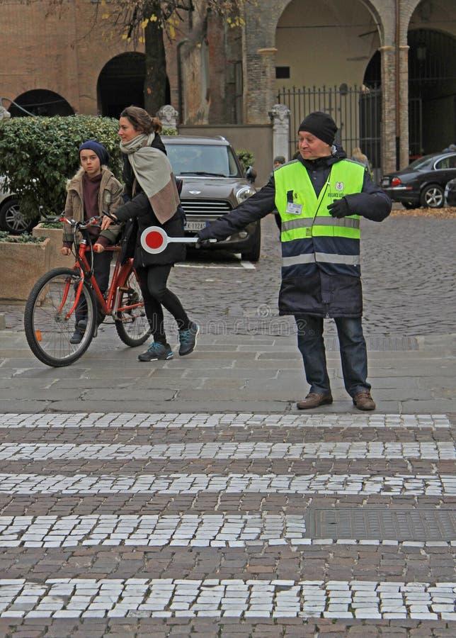 Trafikkontrollanten hjälper till folk på övergångsställe i Padua, Italien arkivbild