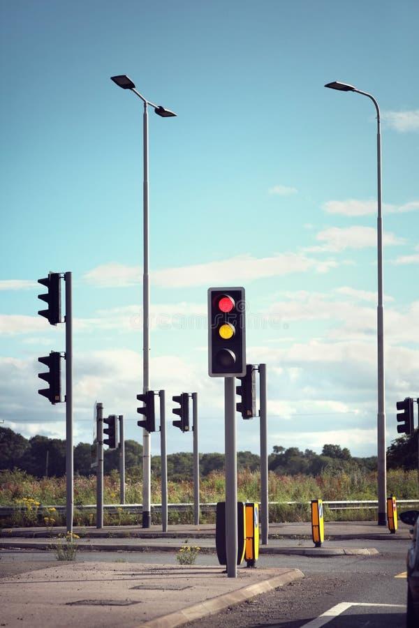 Trafikljus för bilar på en väg som ändrar från rött för att göra grön arkivbild