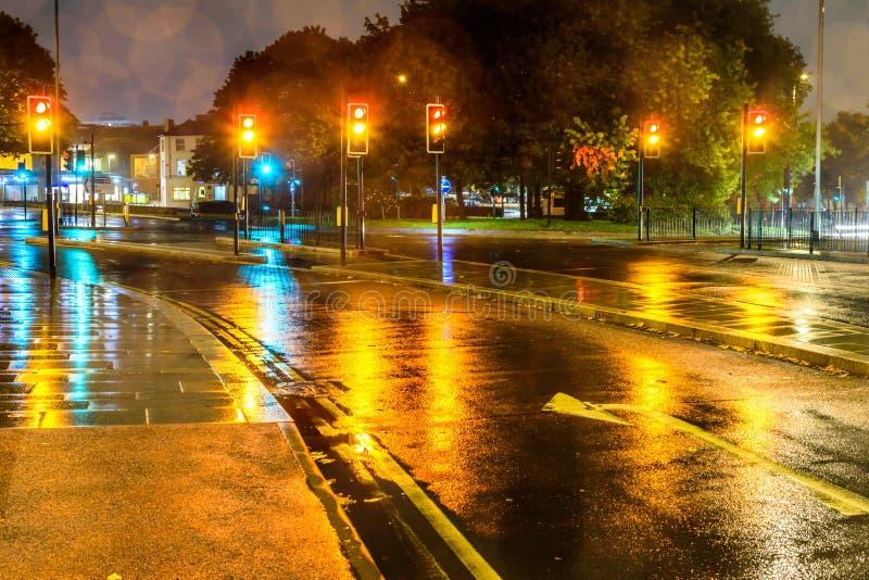 Trafikljus för guling för nattregnsikt på UK-karusellen royaltyfria foton