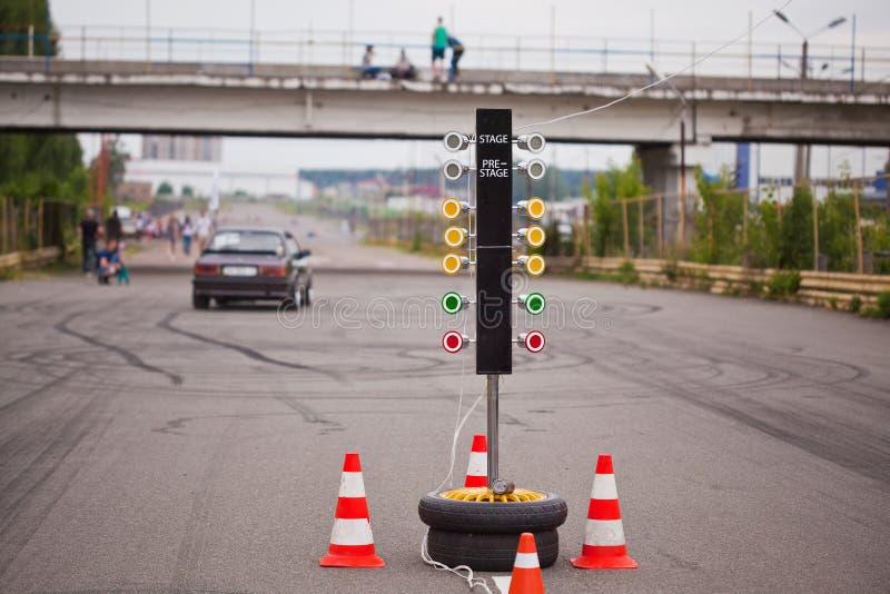 Trafikljus i början av ett tävlings- spår med en bil i avståndet royaltyfri fotografi