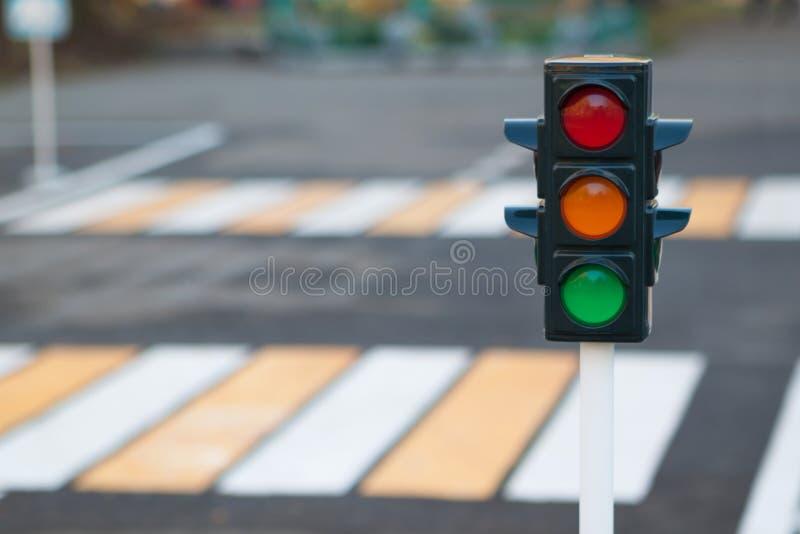 Trafikljus på bakgrunden av vägen och övergångsstället i stad Röd, gul och grön trafikljus Trafiklagar, arkivbild