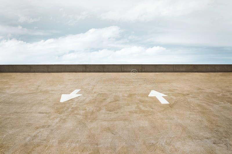 Trafikpilar på ett tak för parkeringsgarage med en molnig himmel royaltyfri foto
