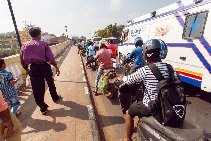 Trafikstockning med cyklar och bilar på den smala bron i asiatisk stad royaltyfria foton