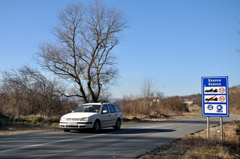 Trafiktecken och vitbil på ingången till republiken av Kosovo från Serbien arkivfoton