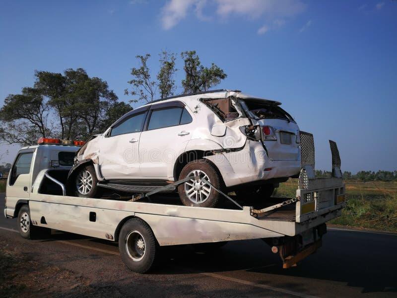 Trafiktjänstemän tar den bogserade bilen på bärgningsbilen bilen laddas in i royaltyfria bilder