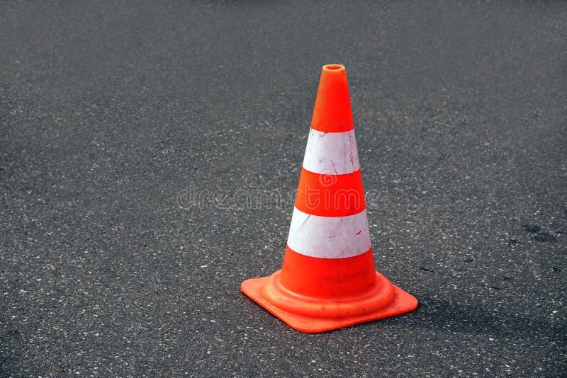 Trafique el cono, el blanco y la naranja en el asfalto gris, espacio de la copia fotografía de archivo