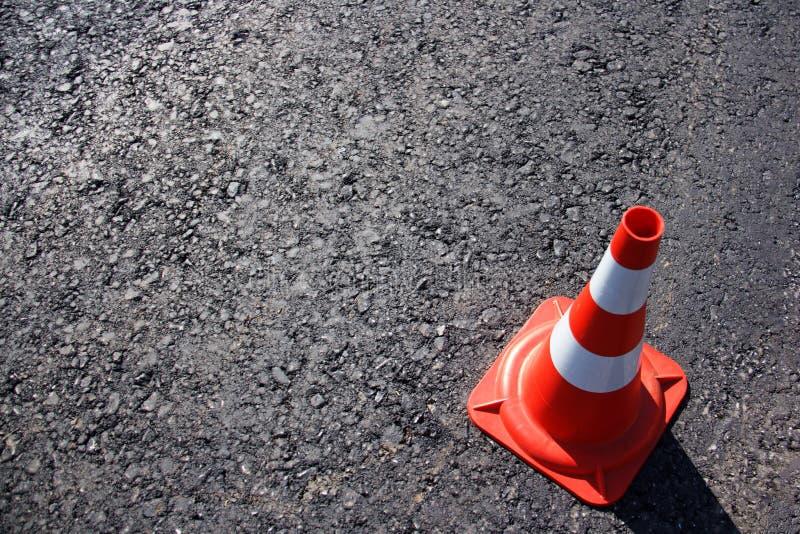 Trafique o cone, com as listras brancas e alaranjadas no asfalto cinzento, espaço da cópia foto de stock royalty free