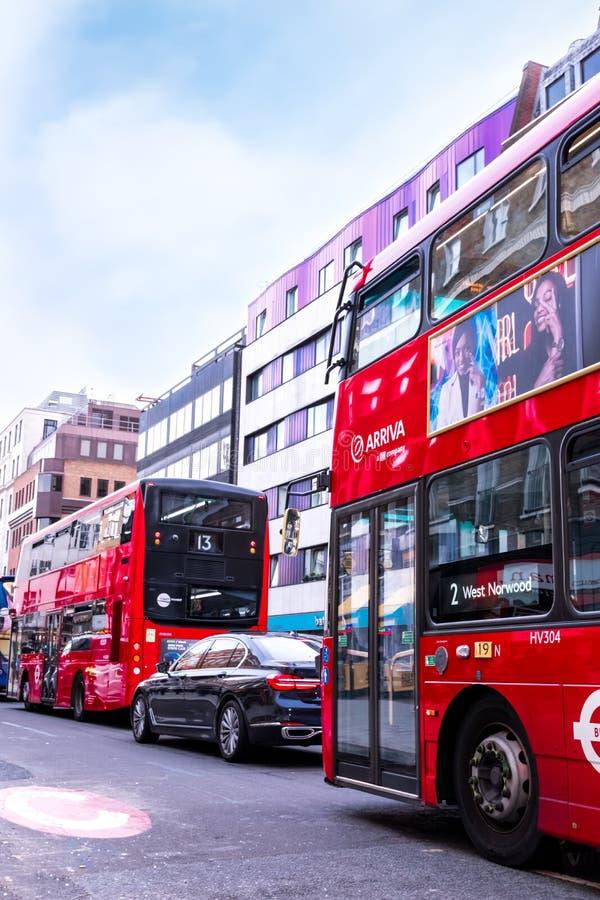 Trafiquez à Londres - deux autobus rouges typiques avec des annonces et Mercedes noir, se tenant dans le trafic images libres de droits