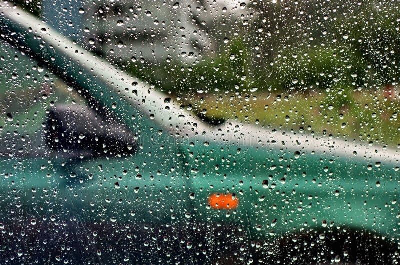 Trafiquez du jour pluvieux avec la vue par la fenêtre de voiture avec des baisses de pluie, beau fond de conception de temps avec images libres de droits