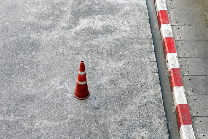 Trafiquez les cônes, rez-de-chaussée de ciment et les cônes du trafic de plastique rouges et les rayures blanches est dispositif  photos stock