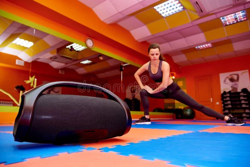 Tragbare Akustik im Aerobicraum auf dem Hintergrund eines unscharfen übenden Sports des Mädchens stockfotos