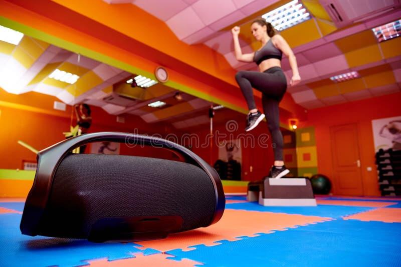 Tragbare Akustik im Aerobicraum auf dem Hintergrund eines unscharfen Mädchentrainings auf einer Schrittplattform lizenzfreie stockfotografie
