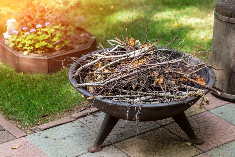 Tragbarer Eisenkamin mit trockenem Reisig am Hinterhof des Sommerhäuschens Feuer vorbereitet für die Glättung von Lagerfeuergesch stockfotos