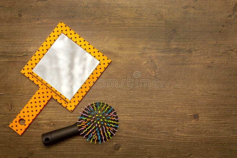 Tragbarer Spiegel und mehrfarbige Haarbürste auf hölzernem Hintergrund, Draufsicht, flache Lage, Kopienraum lizenzfreie stockfotos