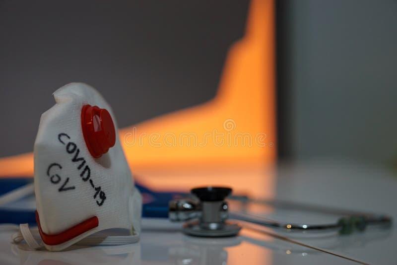 Tragedie atmosfeer, masker met tekst van het coronavirus geschreven Covid-19 en stetoscope Het kweken van geïnfecteerde grafiek o stock foto