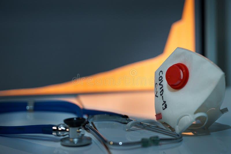 Tragedie atmosfeer, masker met tekst van het coronavirus geschreven Covid-19 en stetoscope Het kweken van geïnfecteerde grafiek o royalty-vrije stock afbeelding