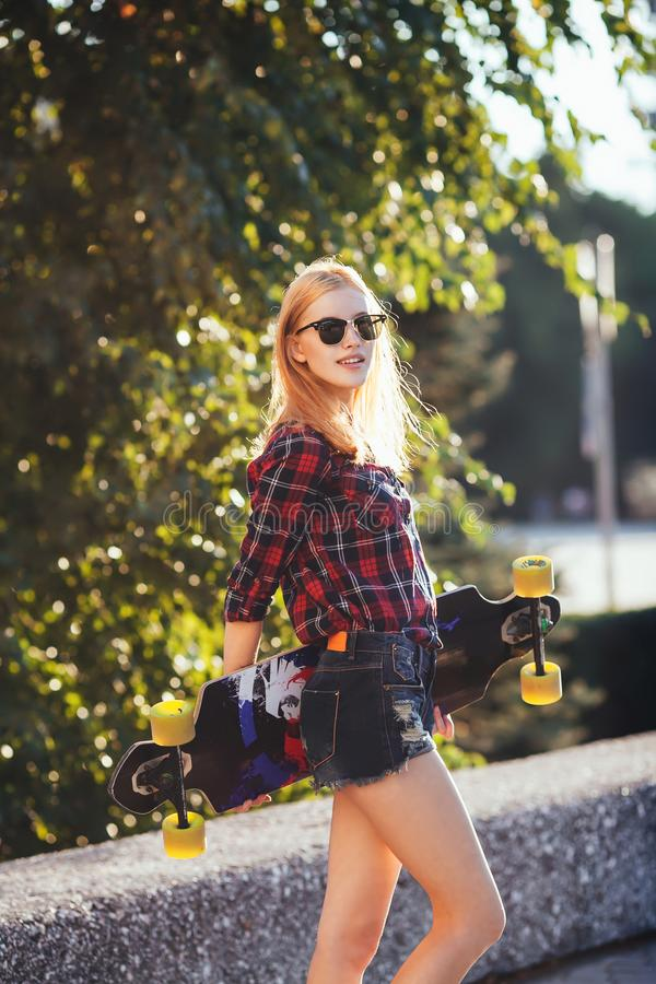 Tragen Sie das glückliche Mädchen zur Schau, das im Sommer mit Skateboard aufwirft Stilvolle glückliche Hippie-Frau mit buntem lo lizenzfreies stockfoto