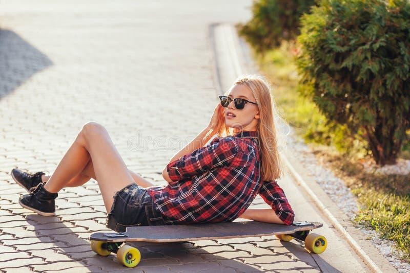 Tragen Sie das glückliche Mädchen zur Schau, das im Sommer mit Skateboard aufwirft Stilvolle glückliche Hippie-Frau mit buntem lo lizenzfreie stockbilder