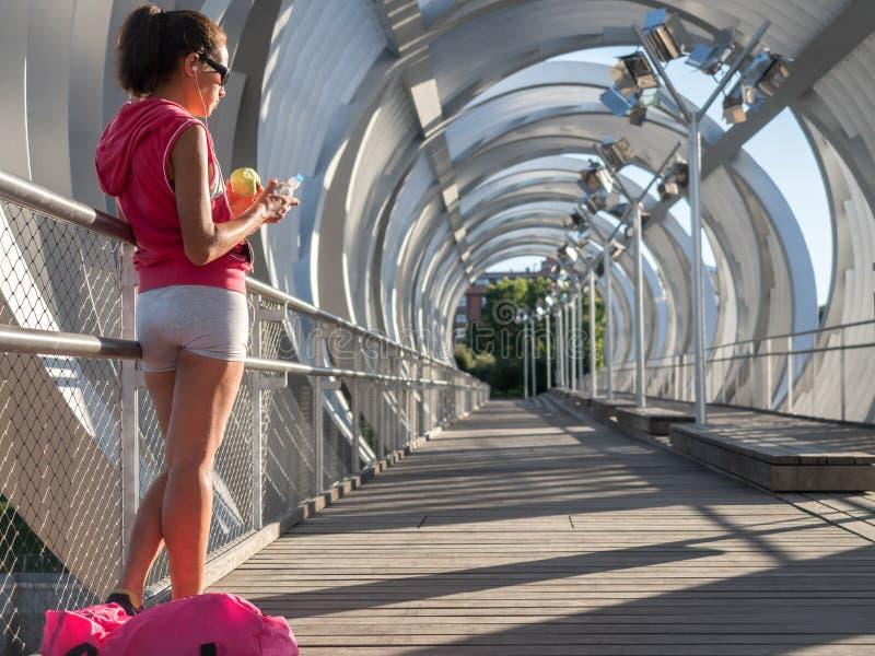 Tragen Sie das weibliche Stillstehen und das Essen eines Apfels beim Hören auf mus zur Schau lizenzfreies stockbild