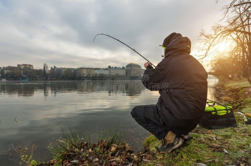 Tragen Sie den Fischer zur Schau, der versucht, Fische im Fluss, städtisches Fischen zu fangen stockfotos
