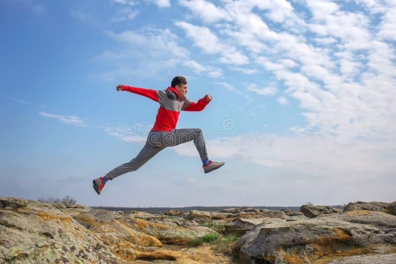 Tragen Sie den Mannbetrieb zur Schau und über Felsen im Berggebiet springen stockfotos