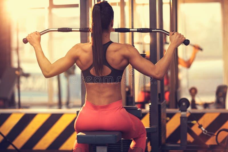 Tragen Sie die Frau zur Schau, die Übung in der Turnhalle, hintere Ansicht tut stockfoto