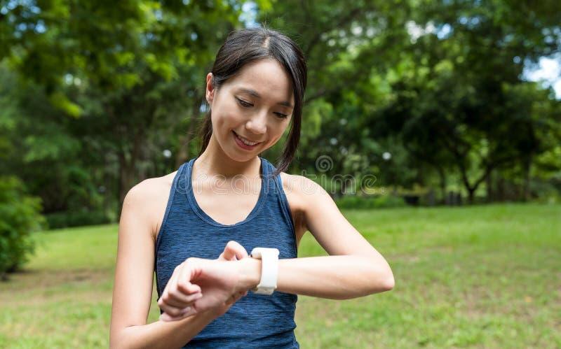 Tragen Sie die Frau zur Schau, die intelligente Uhr im Park verwendet stockfotografie