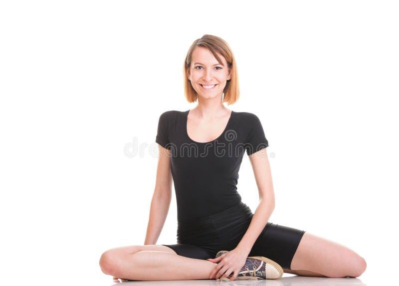 Tragen Sie die junge Frau zur Schau, welche die Übung tut, die auf Weiß lokalisiert wird stockfotos