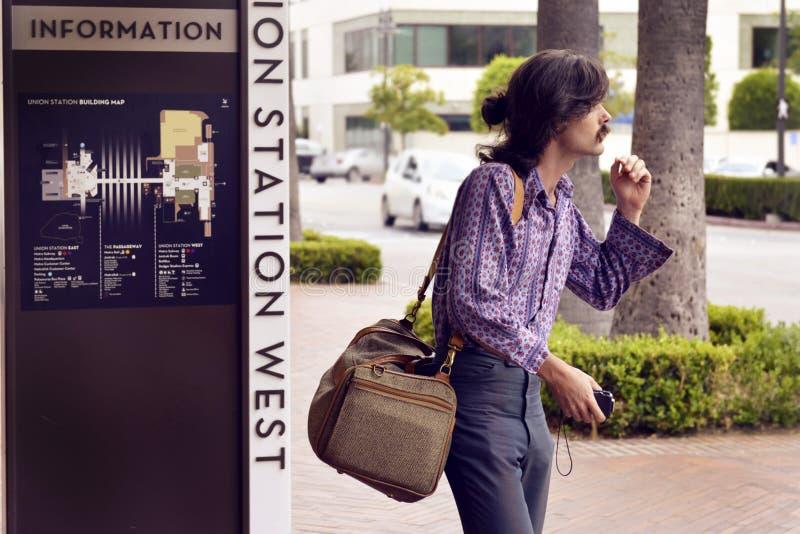 Tragen Sie ein violettes Kleidungshemd und eine schwarze Hose mit weißer, brauner Sling-Tasche stockbilder
